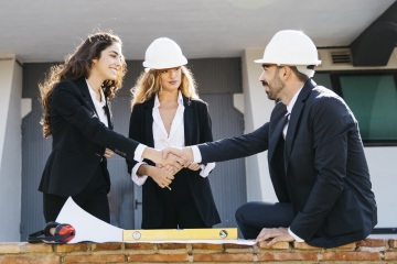Architects Wearing Helmets Shaking Hands