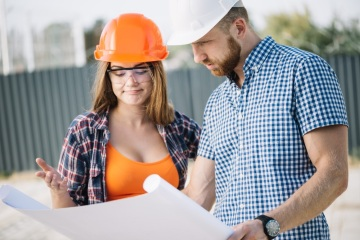 Builder Showing Blueprint to Colleague
